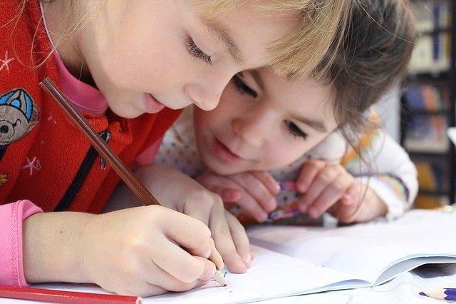 děti skloněné nad sešitem ve škole